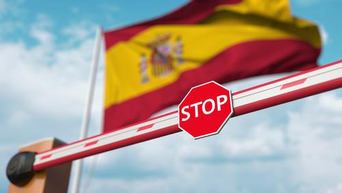 Barrier Tor geschlossen mit der Flagge von Spanien als Hintergrund. Grenzüberschreitung in Spanien oder bestimmtes Verbot. 3D-Rendering, Shutterstock