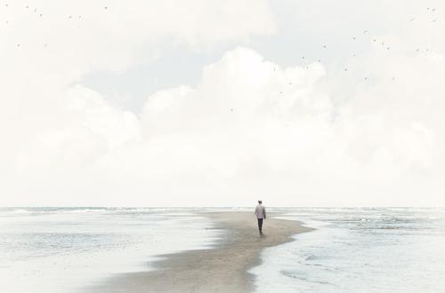 Ruhiger Mann im Sand zwischen zwei Meeren, Shutterstock